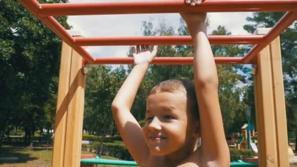 Klettergerüst Am Hang : Lächelnde junge hängen vom klettergerüst auf spielplatz stockfoto
