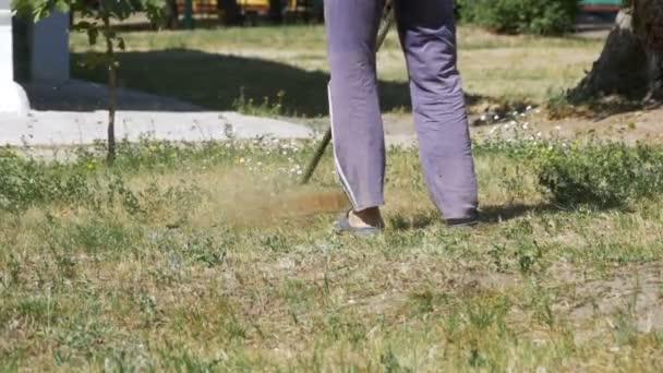 Člověk seká trávu pomocí přenosného sekačka v pomalém pohybu