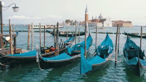 Docked empty gondolas on wooden mooring piles. Venice, Italy