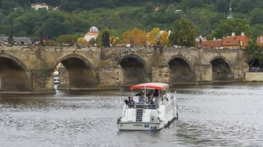 People walk along the old Prague Bridge and Boat Floating on the River Vltava