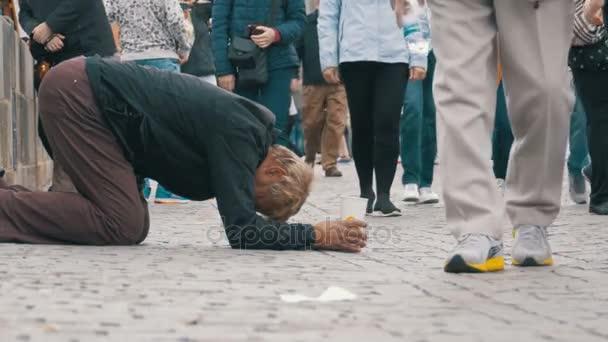 Obdachloser Bettler mit Plastikbecher in der Hand bettelt auf dem Bürgersteig um Almosen von Passanten