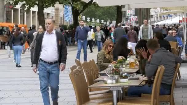 Menschen sitzen an Tischen in einem Straßencafé. München, Deutschland