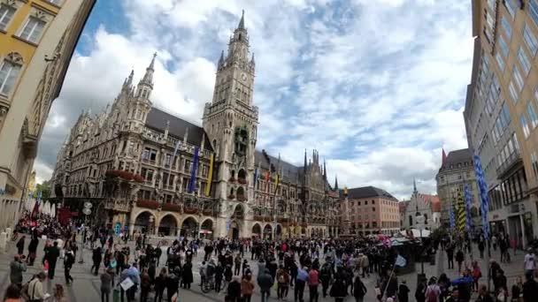 Menschen, die auf dem Marienplatz am berühmten Rathaus spazieren. München, Deutschland