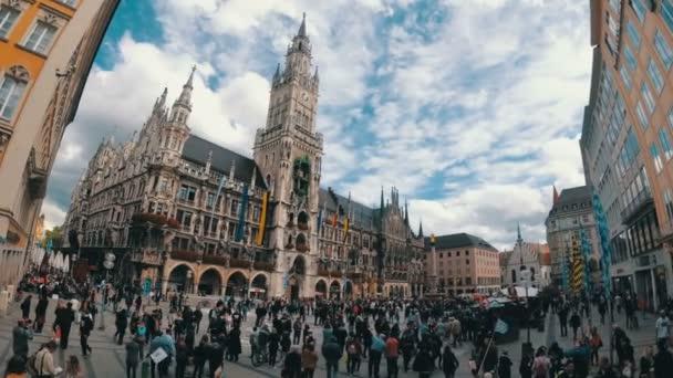 Touristen spazieren auf dem Marienplatz am berühmten Rathaus. München, Deutschland