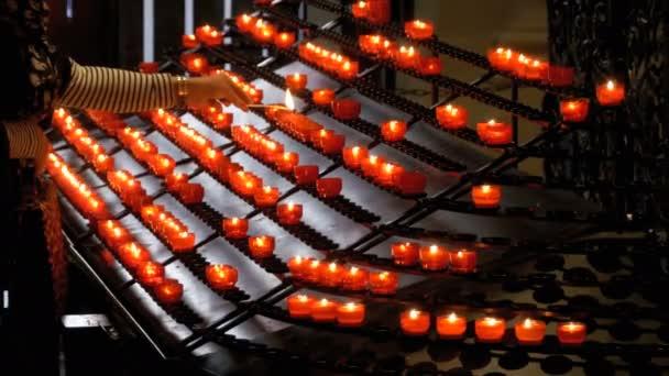 Žena umístí svíčka v křesťanské církvi. Mnoho svíčky jsou rozsvíceny v chrámu