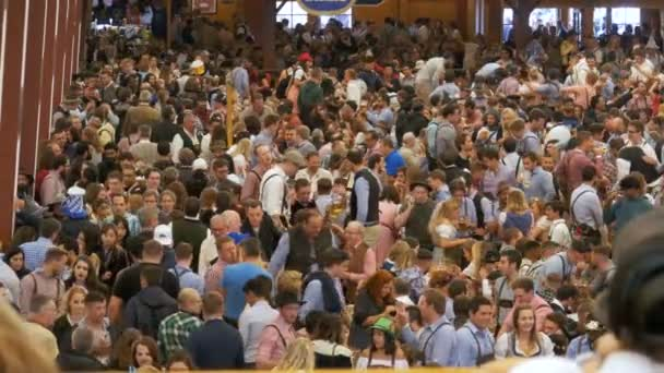 Menge von betrunkenen Menschen feiert Oktoberfest im Inneren ein großes Bierzelt. Bayern, Deutschland