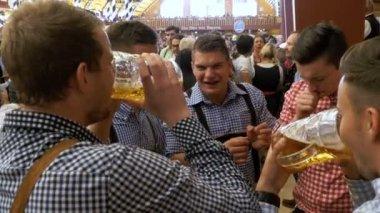 Drunken mens inside a large beer pub with beer mugs in their hands celebrate Oktoberfest. Bavaria, Germany.