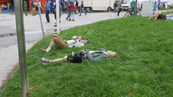 Betrunkene Männer liegen auf dem Rasen in der Nähe der Statue von Bayern auf dem Oktoberfest-Festival. Bayern, Deutschland