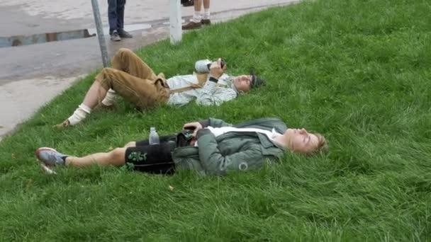 Betrunkene Männer liegen auf der Wiese in der Nähe der Statue von Bayern auf dem Oktoberfest-Festival. Bayern, Deutschland