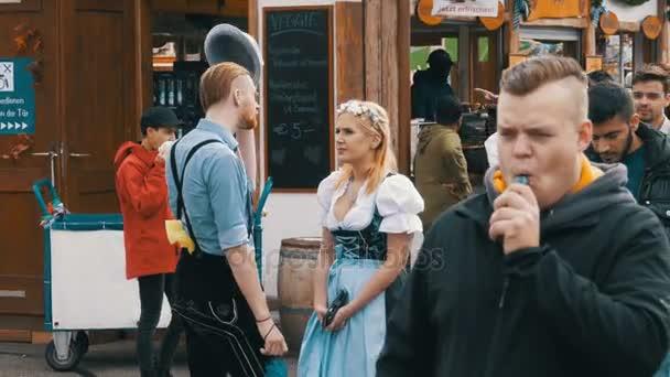 Menschen in bayrischen Trachten laufen über die Straße des Oktoberfests. Bayern, Deutschland