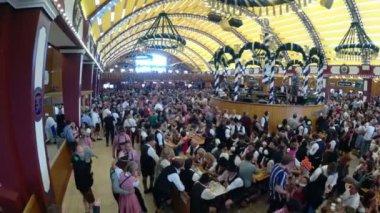 People Celebration of Oktoberfest in large beer tent. Bavaria, Germany