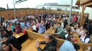 Drunken People at the table celebrate Oktoberfest in a large beer bar on the street. Bavaria, Germany