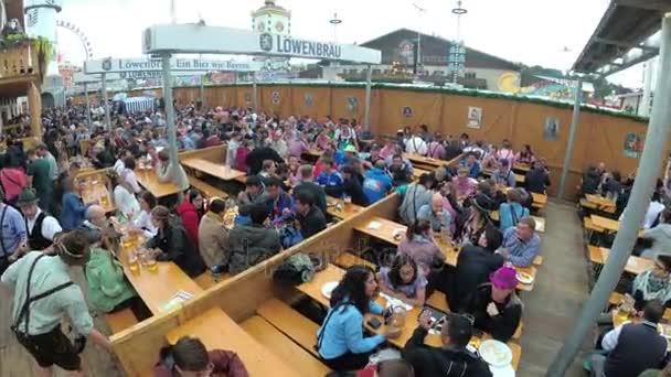 Leute am Tisch feiern Oktoberfest in einer großen Bierbar auf der Straße. Bayern, Deutschland