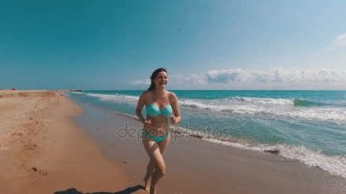 Young Girl Runs along the Beach of the Sea Coast in Slow Motion