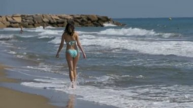 Girl in bathing suit runs along the sea shore at the beach in Slow Motion