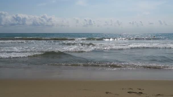 A tenger hullámai gurul a homokos strandon, lassítva