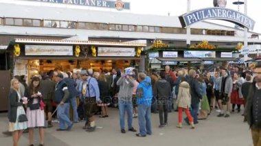 Crowd of People are walking along the central street of the Oktoberfest festival. Bavaria, Germany