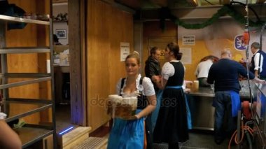 Behind the scenes. Staff, waiters at the Oktoberfest wear beer and wash the dishes in a washing machine