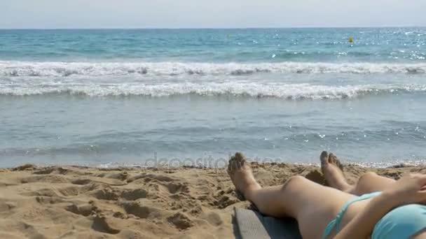 Legs of Woman Lying on Beach near the Sea
