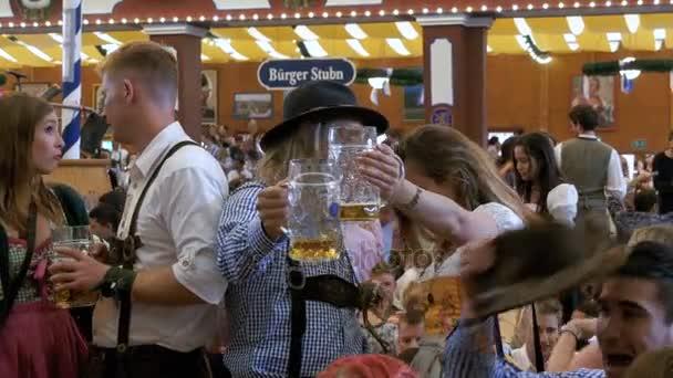 Betrunkene mit einem Krug Bier feiern Oktoberfest in einem großen Bierzelt. Bayern, Deutschland