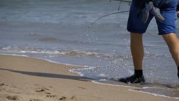 Pescatore con canne da pesca e uno zaino passeggiate lungo la spiaggia di  Riva del mare. Slow Motion– filmato stock 40107d182088