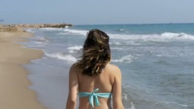 Young Girl Walks along the Beach of the Sea Coast in Slow Motion