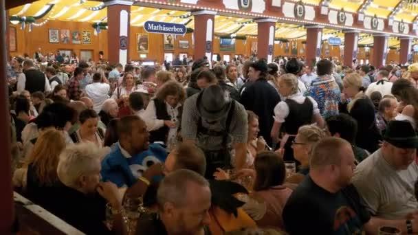 Betrunkene Leute am Tisch feiern Oktoberfest im Inneren ein großes Bierzelt. Bayern, Deutschland