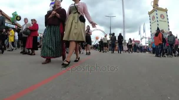 Die Kamera bewegt sich unter Menschenmassen auf der zentralen Straße des Oktoberfests. Bayern, Deutschland