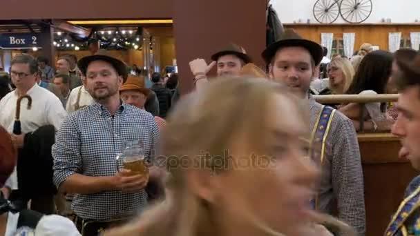 Betrunkene Männer in einer großen Bierkneipe mit Bierkrügen in der Hand feiern Oktoberfest. Bayern, Deutschland.