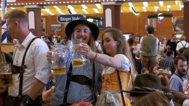 Betrunkene Frauen und Männer mit einem Krug Bier feiern Oktoberfest in einem großen Bierzelt. Bayern, Deutschland
