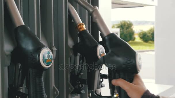 Ženská ruka pomocí palivové trysky na benzinové pumpě. Čerpací stanice. Čerpací stanice.