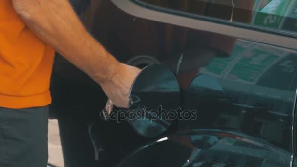 Plnění auto s plynem. Mans ručně pomocí benzinová pumpa k vyplnění jeho auto s palivem