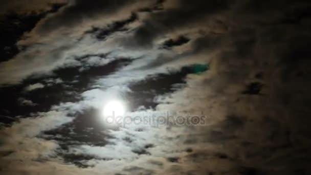 Vollmond wandert durch die Wolken am Nachthimmel. Zeitraffer