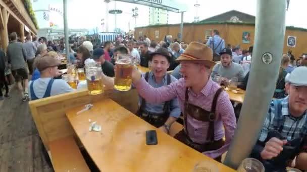Betrunkene Leute am Tisch feiern Oktoberfest in einer großen Bierbar auf der Straße. Bayern, Deutschland