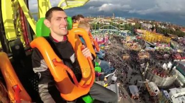 Emotions of people sitting on Sky fall Tower attraction in free fall down on Oktoberfest. Bavaria.