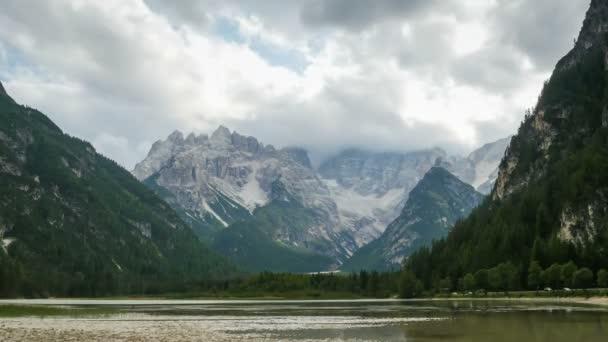 Mraky se pohybují nad vrcholky alpských hor a horské jezero. Časová prodleva