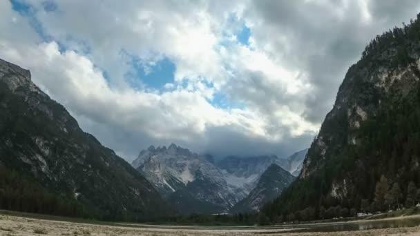 Felhők haladnak át a csúcsok az alpesi hegyek és a hegyi tó. Idő telik el