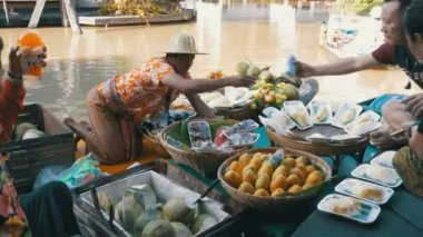 Asian salesman on small boat with fruits and vegetables sells the goods. Pattaya Floating Market