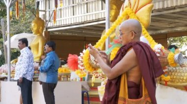 The monk uses mobile phone with a touchscreen in the temple of golden Buddha. Thailand