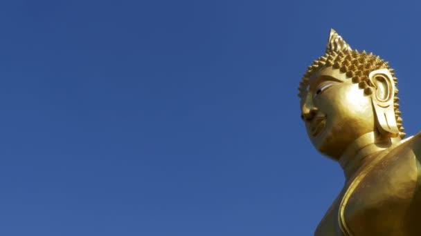 Socha velkého zlatého Buddhy proti modré obloze v Thajsku chrámu. Pattaya