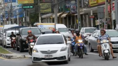 Motorbikes and cars drive along Asian roads. Traffic-laden Thai streets. Thailand, Pattaya