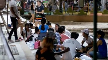 Asian people sitting on sidewalk eat food are in the evening near the sea on the embankment under palm trees