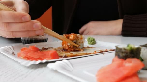 Žena jí Sushi Rolls s hůlkami v japonské restauraci