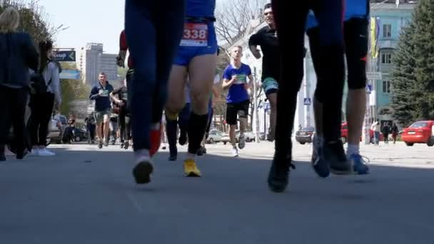 Legs Crowd of People and Athletes Runners Run along the Road in the City