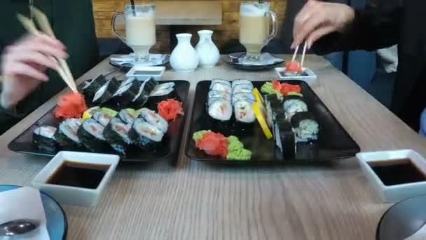 Skupina lidí v restauraci jíst velké sushi set u stylového stolu. Časová prodleva