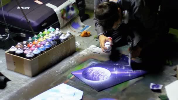 Utcai Graffiti művész fest egy képet használ a Spray-festék éjjel