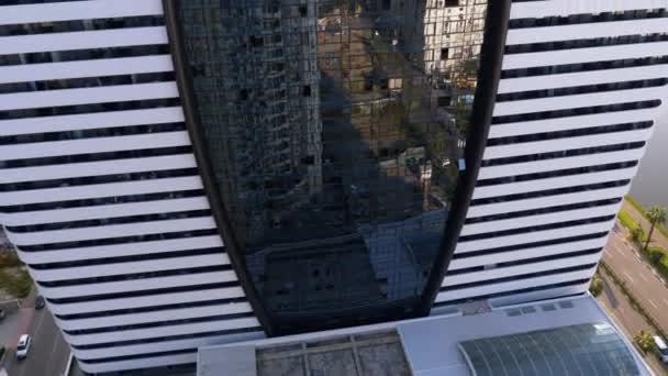 Moderní vícepodlažní stylová budova s mnoha okny a podlahami. Reflexe města v oknech