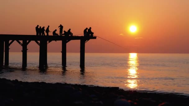 Silhouettes of Fishermen with Fishing Rods at Sea Sunset Sitting on the Pier. Slow Motion.