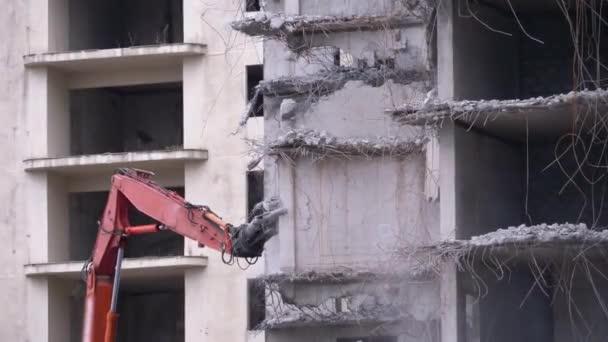 Zničení starého železobetonového domu pomocí mechanického ramene buldozeru na staveništi