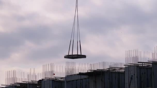 Building construction. A Crane on a Construction Site Lifts a Load.